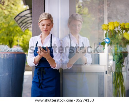 Portrait of beautiful caucasian girl self-employed in flower shop, smiling and using mobile phone. Horizontal shape, waist up - stock photo