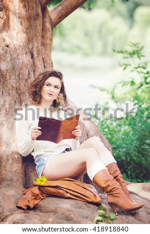 Portrait of beautiful Caucasian girl woman with long dark red brown hair, in shorts and sweater, sitting in summer park forest outside reading book dreaming, looking up, toned with Instagram filters - stock photo