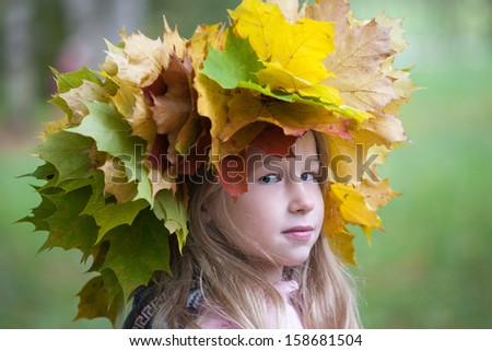 portrait of beautiful caucasian little girl in yellow autumn maple leaves crown