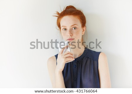 Portrait of beautiful Caucasian redhead girl browsing Internet on smart phone, looking at the camera. Young female freelancer with red hair using electronic gadget for working on her project indoor - stock photo