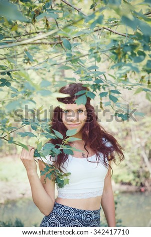 Portrait of beautiful Caucasian woman girl with long red wavy hair in white top, with brown hippie style headband standing in forest park outside in summer spring, smiling looking directly into camera - stock photo