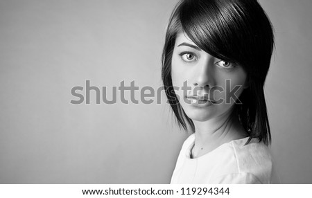 Portrait of beautiful caucasian woman with beautiful dark hair posing on grey background - stock photo