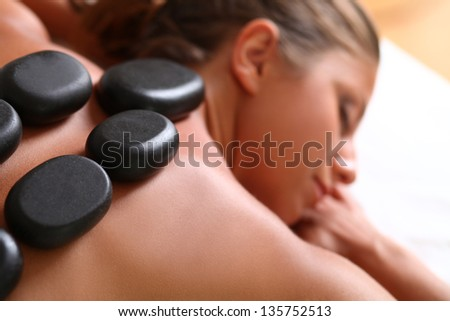Portrait of beautiful caucasian woman with spa stones on her back