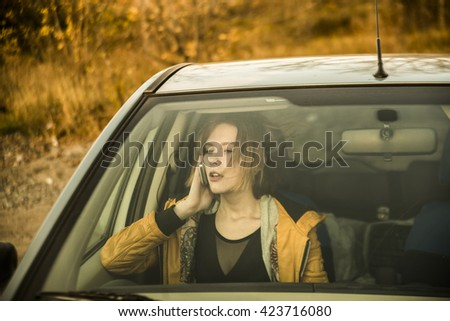 Portrait of beautiful caucasian  young woman holding in hands cell mobile phone inside new car through transparent window background. Copy space for inscription. Taxi Girl call customer. Empty place