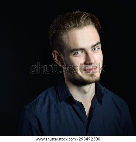 Portrait of beautiful charming young man with blue eyes and fair hair over black background