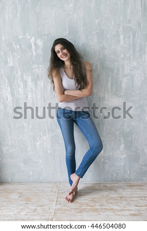 Portrait of beautiful cheerful girl with long brunette hair posing barefoot on wooden floor and cement gray wall - stock photo