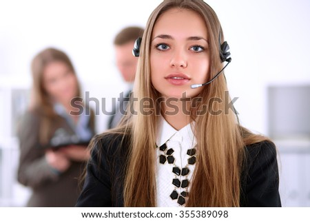 Portrait of beautiful cheerful smiling call operator on the background of business people. Successful call center concept - stock photo