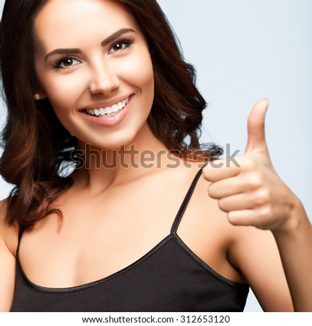 Portrait of beautiful cheerful smiling woman showing thumb up hand sign gesture, over bright grey background, square composition - stock photo