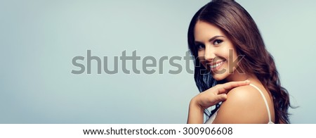 Portrait of beautiful cheerful smiling young woman in white tank top clothing, with blank copyspace area for text or slogan - stock photo