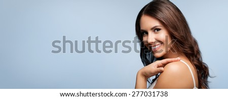 Portrait of beautiful cheerful smiling young woman, on grey, with blank copyspace area for text or slogan - stock photo