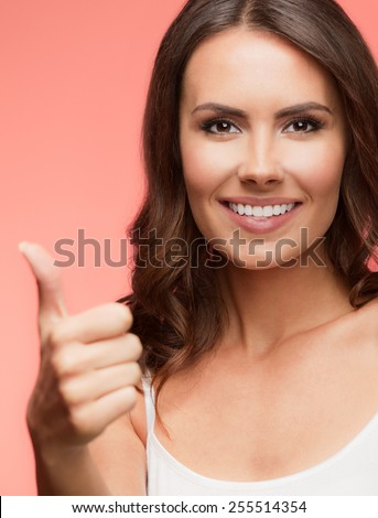 Portrait of beautiful cheerful smiling young woman showing thumb up gesture, on red background - stock photo