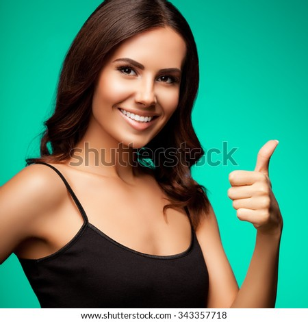 Portrait of beautiful cheerful smiling young woman showing thumb up hand sign gesture, over bright green background - stock photo
