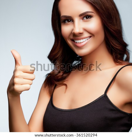 Portrait of beautiful cheerful smiling young woman showing thumb up hand sign gesture, over bright grey background, square composition - stock photo