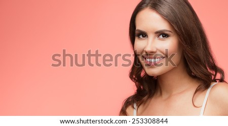 Portrait of beautiful cheerful smiling young woman, with blank copyspace area for text or slogan, on red background - stock photo