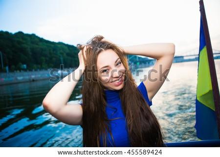 Portrait of beautiful cheerful woman posing near the river - stock photo