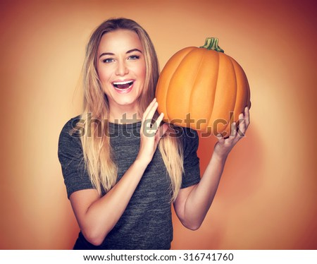 Portrait of beautiful cheerful woman with pumpkin over orange background, celebrating happy Thanksgiving day  - stock photo