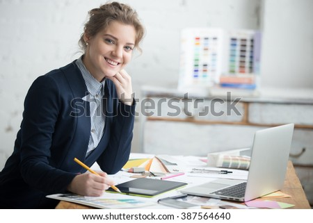Portrait of beautiful cheerful young designer woman working at home office desk. Attractive model wearing suit holding pencil and looking at camera with friendly expression. Interior shot