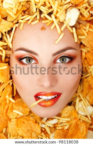 portrait of beautiful cheerful young female face with unhealthy eating fast food potato chips and rusk frame - stock photo