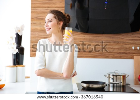 Portrait of beautiful cheerful young woman drinking juice on the kitchen - stock photo