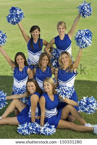 Portrait of beautiful cheerleaders holding pompoms on field - stock photo