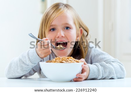 Portrait of beautiful child having breakfast at home.