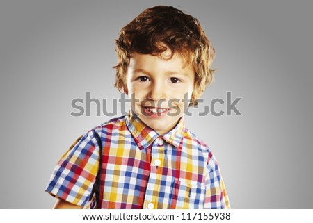 Portrait of beautiful child smiling. Happy laughing little boy isolated on grey background - stock photo