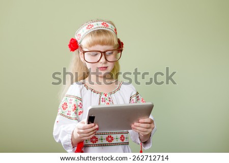 Portrait of beautiful child young lady in handmade embroidered dress and colorful wreath with tablet pc computer - stock photo