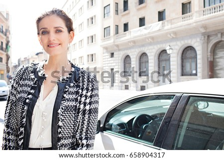 Portrait of beautiful classic elegant business woman smiling looking at camera by classic office buildings and car. Professional working female, confident and trustful. Banking boss woman. Lifestyle.