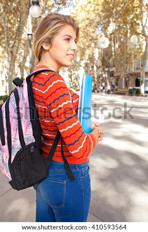 Portrait of beautiful college student in a city avenue with trees and stone pavement, carrying school folders and a backpack, smiling outdoors. Student lifestyle, sunny street exterior. - stock photo
