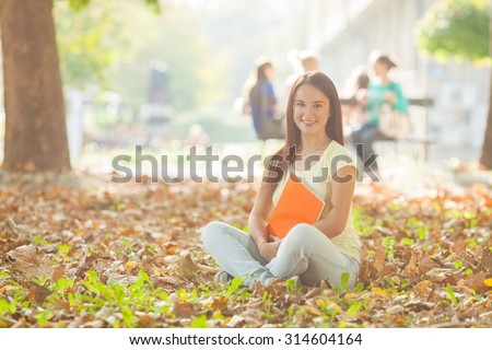 Portrait of beautiful college student sitting on the ground in a university campus on a sunny autumn day