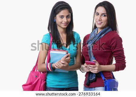 Portrait of beautiful college students with books and bags against white background - stock photo