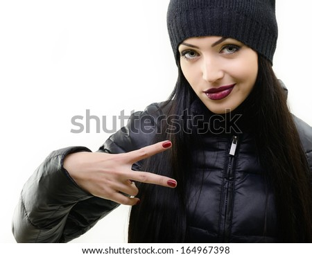 portrait of beautiful cool girl gesturing in black hat and jacket over white - stock photo