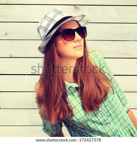 Portrait of beautiful cool girl gesturing in hat and sunglasses  - stock photo