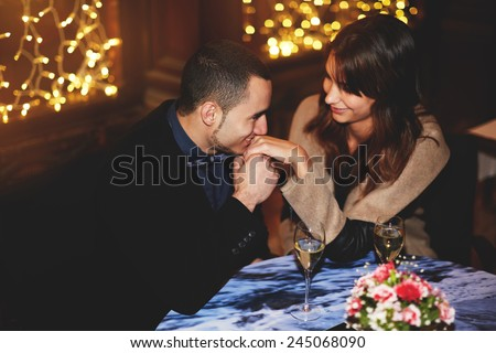 Portrait of beautiful couple enjoying each other's company in a romantic dinner, boyfriend kissing his girlfriend's hand  in restaurant - stock photo