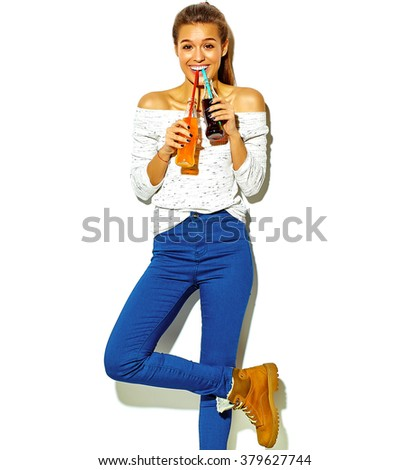 portrait of beautiful crazy smiling brunette woman girl in casual blue hipster summer clothes with no makeup isolated on white drinking soda from two bottles with straw - stock photo