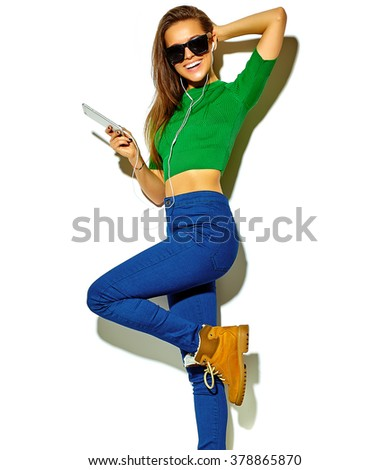 portrait of beautiful crazy smiling brunette woman girl in casual green hipster summer clothes with no makeup isolated on white in sunglasses listening music in smartphone with headphones - stock photo
