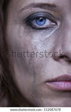 portrait of beautiful crying girl with smeared mascara  - stock photo