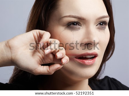 portrait of beautiful crying girl with smeared mascara drying her tears and smearing lipstick - stock photo