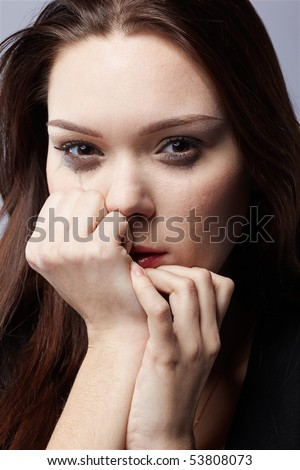 portrait of beautiful crying girl with smeared mascara hiding her face in hands - stock photo