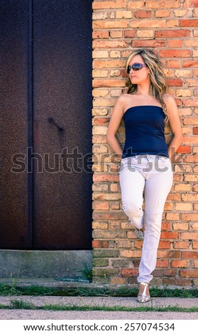 Portrait of beautiful curly blonde girl with black top and sunglasses posing over a metal door background - stock photo