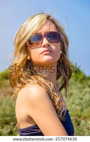 Portrait of beautiful curly blonde girl with black top and sunglasses posing over a nature background - stock photo