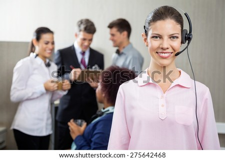Portrait of beautiful customer service representative standing at office while team discussing in background - stock photo
