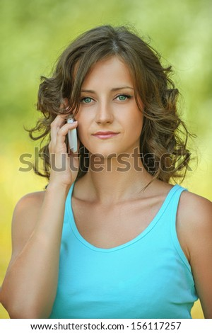 Portrait of beautiful dark-haired curly young woman wearing blue t-shirt, speaking on mobile phone at summer green park.