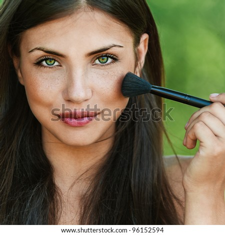 portrait of beautiful dark-haired sexy girls with makeup brush in hand on green background - stock photo