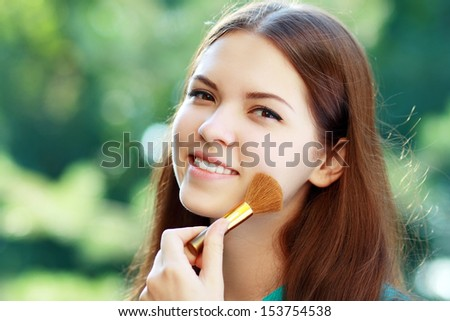 portrait of beautiful dark-haired teen girl with makeup brush in hand on green background