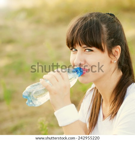 Portrait of beautiful dark-haired woman wearing white t-shirt drinking water at summer green park after jogging. - stock photo