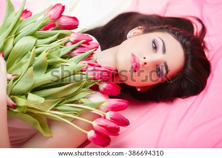 Portrait of beautiful dark-haired woman with  tulip bouquet. Spring portrait. beauty