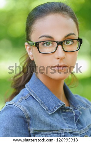 Portrait of beautiful dark-haired young woman in denim jacket and glasses with black frame, against summer green park. - stock photo