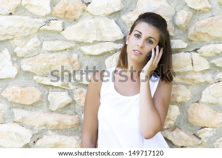 Portrait of beautiful dark-haired young woman wearing white t-shirt, calling with the mobile - stock photo