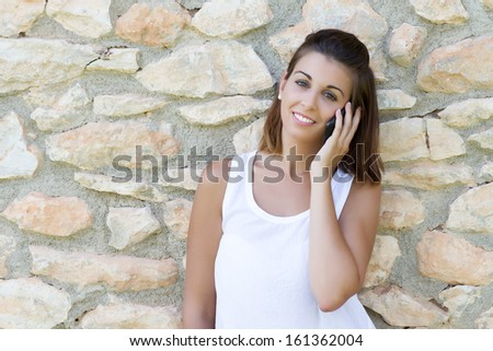 Portrait of beautiful dark-haired young woman wearing white t-shirt, speaking with the mobile - stock photo
